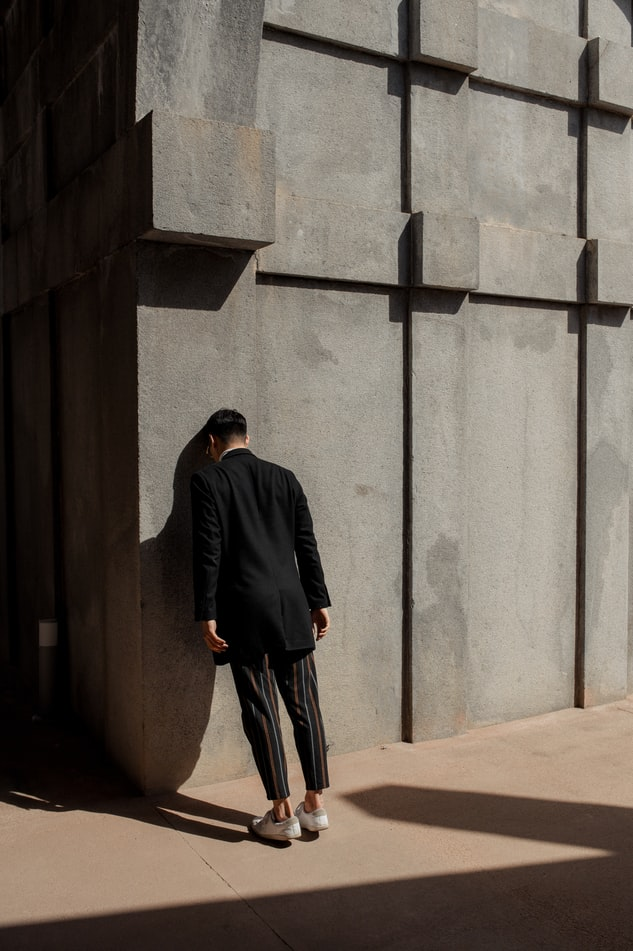 Man leaning against a wall in frustration
