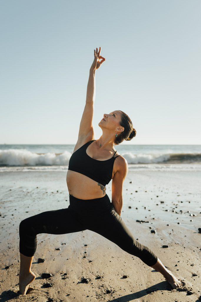 Yoga teacher doing a pose on the beach.