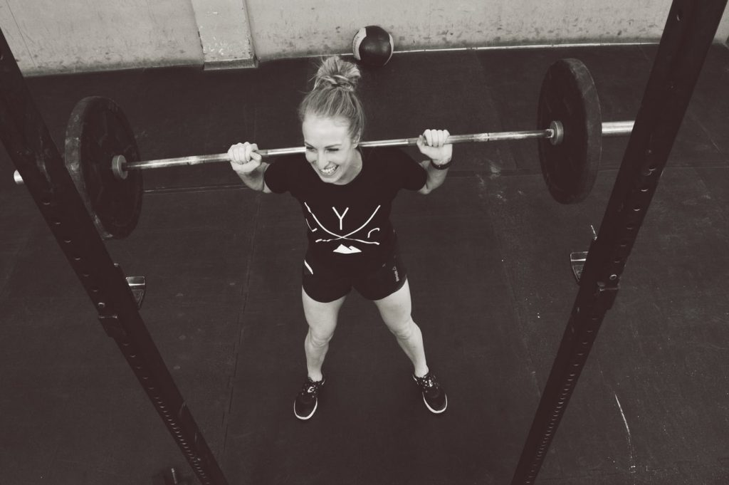 A black and white image of a woman smiling with a barbell across her shoulders