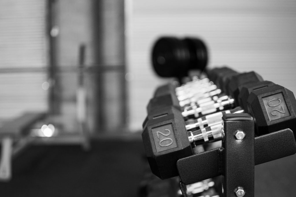 A black and white image of dumbells lined up in an empty gym